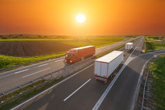 Speed delivery trucks on the empty highway at sunset Royalty Free Stock Image