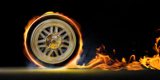 Speed and fire. Car wheel on fire and smoke on black background Royalty Free Stock Images