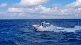 Speed fishing tender boat jumping the waves in the sea and cruising the blue ocean day in Bahamas. Blue beautiful water royalty free stock image