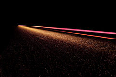 Speed of Light. A Streek of light ending in the horizon with a trail of specks Stock Photos