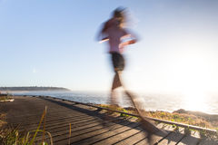 Speed of light. A runner on a boardwalk in the morning Royalty Free Stock Photography