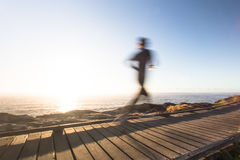Speed of light. A runner on a boardwalk in the morning Royalty Free Stock Photos