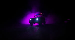 Speed lighting of police car in the night on the road. Police cars on road moving with fog. Selective focus. Chase. Speed lighting of police car in the night on stock photo