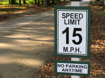 Speed limit 15mph. Speed limit 15 mph sign with o parking anytime on bottom on a shady scenic roadway with fall leaves stock photography