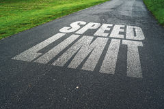 Speed Limit message reminder on asphalt road Stock Images