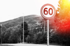 60 speed limit road sign with light leak background Stock Photo