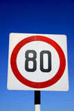 Speed limit sign. A road signboard bearing number 80 with red circle shows a speed limit of not more than 80, with blue sky background Stock Photos