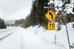Speed Limit Sign along a Snowy Winding Mountain Road stock image