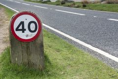 Speed limit sign on grass verge by side of road Royalty Free Stock Photo
