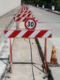 Speed limit sign and hurdles in the road excavation Stock Photography