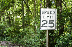 Speed limit sign surrounded by a wooded area Stock Image