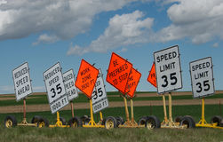 Speed Limit Signs. Construction zone signs against a blue cloud filled sky setting near some farmland stock images