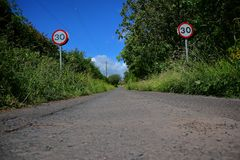 Speed limit signs and road. Blue sky and some trees Royalty Free Stock Photos