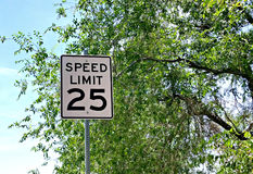 Speed Limit 25. Traffic sign with Speed Limit 25 with a blue sky and tree in the background Royalty Free Stock Image