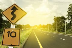Traffic sign,10 MPH and winding road caution symbol for safety drive in the country black road, sky with toned color royalty free stock photo