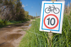 Speed limitation to bikes. Road with signboard about bicycle speed limitation Stock Photo