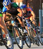 Speed race on bikes. Bikes speed down the roadway in the pro race at the urban professional Criterium bicycle race in the city streets, USA Cycling event Royalty Free Stock Photo