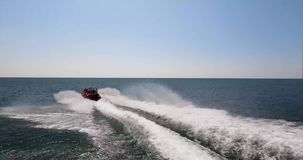 Speed and sea. A high-speed bright boat at high speed sail past the camera leaving a foamy footprint. Passenger boat is delighted stock video footage