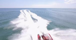 Speed and sea. A powerful red boat sailing directly on the camera. He swims under the camera and leaves a foamy footprint on his own stock footage
