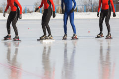 Speed skating competition on ice rink at winter sunny day - sportsmen ready for start. Telephoto Stock Photo