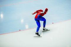Speed skating male athlete. Speed skater on turn ice arena Stock Image