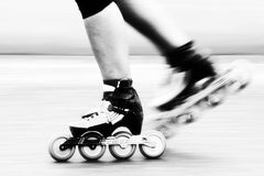 Speed skating. A roller skater is racing down the road, detail of leg and skates Royalty Free Stock Photography