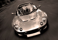 Speed Spirit II. A sexy sportscar rushes towards the objective in a black-and-white close-up Stock Photos