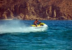 Speed Sport Water. Man on wave running motor boat.  He moving very quickly.  There is a large spray of water behind the boat.  The water is deep blue Stock Photos