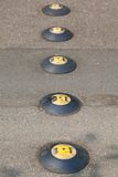 Speed stops in line. 5 black and yellow speed stops on street in line Royalty Free Stock Image