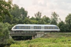 Speed train on railway at the country landscape Stock Photos