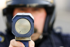 Speed trap. A motorcycle police officer pointing his radar gun at a speeder Stock Photography