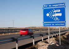 Speed trap sign with car passing. Spanish road sign announcing a speed trap Royalty Free Stock Photography