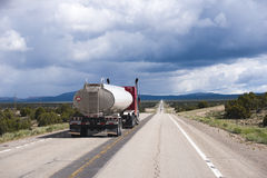 Speed up red semi truck rig with tank trailer on long road in Ne Stock Image