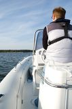 Speedboat 13. Captain at the steering wheel of a modern speedboat with coastline in the background Royalty Free Stock Images
