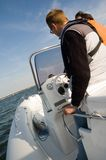 Speedboat 13. Captain at the steering wheel of a modern speedboat with coastline in the background Stock Photo