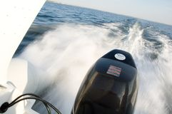 Speedboat 6. Engine bay of a rushing speedboat. Coastline in the background. Tilted horizon and slower shutter speed for a more dynamic look Royalty Free Stock Images