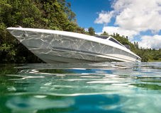 Speedboat on calm lake. WS: Low angle (water level) shot of a very sleek white 7m - 21ft speedboat at rest on calm lake surface with native (NZ) bush in bkgd Royalty Free Stock Photography
