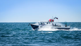 Speedboat in Choppy Sea. A speedboat, skimming the water and sending up sea spray as it hits the water Royalty Free Stock Photo