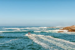 Speedboat exiting the mouth of the Storms River Royalty Free Stock Images