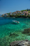 Speedboat moored in turquiose bay in Kephalonia with houses on t Stock Images