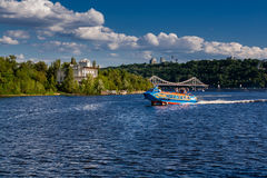 Speedboat sails on the river against the beautiful sky Royalty Free Stock Images