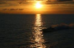 Speedboat Sunset. A speedboat buzzes the coastline at sunset near the Ventura Pier in California stock photo