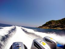 A speedboat with three engines sailing back to shore quickly tha. T made the white wave interspersed with the deep blue sea Stock Image