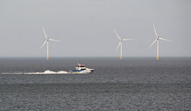 Speedboat and windfarms Royalty Free Stock Images