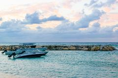 Speedboats/ Motorboats docked on the beach at sunset on tropical Caribbean island. Holiday luxury resort setting. royalty free stock photos