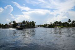 Speedboats Pass Luxury Homes on the Intracoastal. Two speedboat travel to and fro passing luxury homes on the Intracoastal Waterway in a hot summer afternoon in Royalty Free Stock Images
