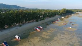 Speedboats standing on sand in low tide water HD aerial view. Rawai beach at Phuket Island, Thailand. stock video footage