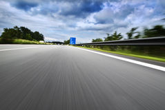 Speeding on autobahn. Motion blur shot while driving fast on autobahn royalty free stock photo