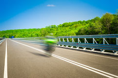Speeding bike on a straight road. Speeding motor bike on a straight road on a sunny summer day with green trees on the background Royalty Free Stock Photo