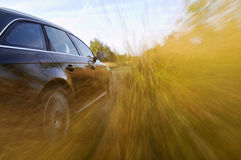 Speeding black car. Side of a speeding black car. Motion blur Royalty Free Stock Photography